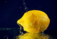 Whole lemon with stopped motion water drops Stock Photos
