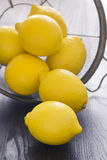 Whole Lemons Spill Out of Colander Royalty Free Stock Image