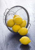 Whole Lemons Spill Out of Colander Stock Images
