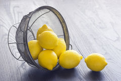 Whole Lemons Spill Out of Colander Stock Photography