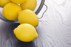 Whole Lemons Spill Out of Colander Stock Photos
