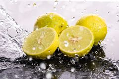 Whole lime and halves, close-up slices with water splashes.  royalty free stock image