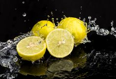 Whole lime and halves, close-up slices with water splashes.  stock photo