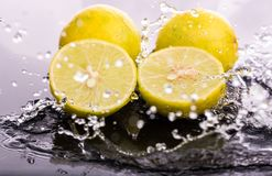 Whole lime and halves, close-up slices with water splashes.  stock photos