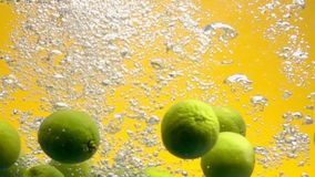 Whole limes falling into water stock video footage