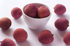 Whole litchis. In white bowl and scaterred on white background Stock Image