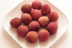 Whole litchis. On white plate and white background Stock Photography