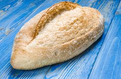 Whole loaf bread with crisp on wooden background top view royalty free stock photo
