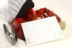 Lobster in Chefs Hat with Recipe Card. Whole lobster wearing a chefs hat holding a blank recipe card with crackers and mallet Royalty Free Stock Photo