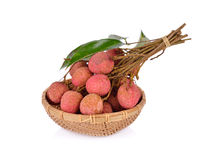 Whole lychee fruit with stem and leaves in basket on white backg Stock Photo