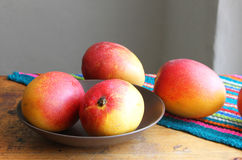 Whole Mangos on a Table. Whole, ripe mangos on a table with colorful place mat and with selective focus on mangos in foreground Stock Photo