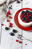 Whole mini cheesecake with blackberries, blueberries and red currant on plate Stock Image
