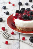 Whole mini cheesecake with blackberries and red currant on plate and berries on table Stock Photography
