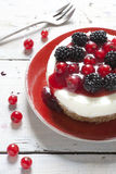 Whole mini cheesecake with blackberries and red currant on plate and berries on table Royalty Free Stock Photo