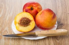 Whole nectarines, half of nectarine and knife in plate Stock Images