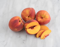 Whole nectarines with a slice on a cutting board. Royalty Free Stock Photography