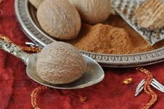 Whole nutmeg and nutmeg powder on spoon and plate. Macro Royalty Free Stock Image