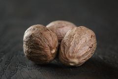 Whole nutmegs in olive bowl on oak table Royalty Free Stock Photography