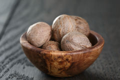Whole nutmegs in olive bowl on oak table Royalty Free Stock Images
