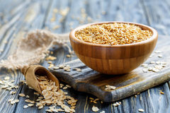 Whole oats in a bowl and oat flakes in a wooden scoop. Oats in bowl and oat flakes in a wooden scoop on an old table, selective focus Royalty Free Stock Image