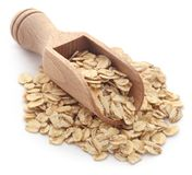 Whole oats. In wooden scoop over white background stock image