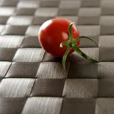 Whole one cherry tomato. Close up of whole one cherry tomato over a brown tablecloth royalty free stock photos