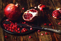 Whole and Opened Pomegranates on Metal Plate. Opened Pomegranate and Whole One wiith Seeds on Metal Plate and Vintage Knife. Some Seeds and Pieces Scattered on Royalty Free Stock Images