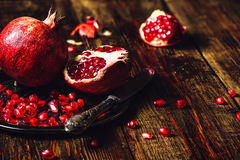 Whole and Opened Pomegranates on Plate. Opened Pomegranate and Whole One wiith Seeds on Metal Plate and Vintage Knife. Some Seeds and Pieces Scattered on Wooden Royalty Free Stock Photos