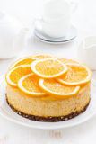 Whole orange cheesecake on a plate Stock Photos