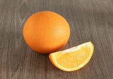 Whole orange next slice on wooden background close up stock photos