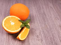 Whole orange next to which slices are cut on a wooden surface stock photo