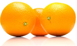 Whole oranges. The ripe whole oranges with real reflexion on white, shallow DOF. Isolation Stock Images