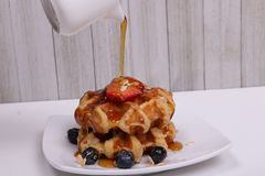 Whole organic oat waffles with strawberries blueberries and maple syrup stock image