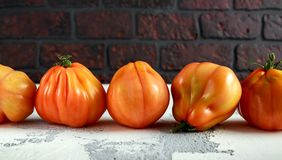 Whole organic tomatoes Coeur De Boeuf. Beefsteak tomato on white rustic table royalty free stock images