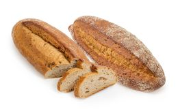 Whole and partly sliced brown bread with sprouted wheat grains. One whole and one partly sliced oval loaf of the wheat and rye sprouted bread with added whole Stock Image