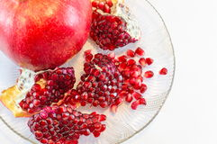 Whole and parts of pomegranate on a plate Stock Images
