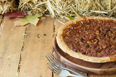 Whole Pecan Pie. On a wooden plate Royalty Free Stock Photography