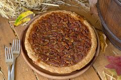 Whole Pecan Pie. On a wooden plate Royalty Free Stock Images