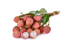 Whole and peeled lychee fruit with stem and leaves on white back Royalty Free Stock Photography