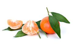 Whole and peeled mandarines with leaves Royalty Free Stock Image