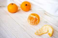 Whole and peeled tangerines. On white boards Stock Images