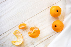 Whole and peeled tangerines. On white boards Royalty Free Stock Photos