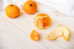 Whole and peeled tangerines. On white boards Royalty Free Stock Images