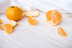 Whole and peeled tangerines. On white boards Royalty Free Stock Image