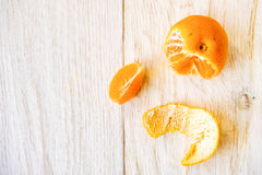Whole and peeled tangerines. On white boards Stock Image