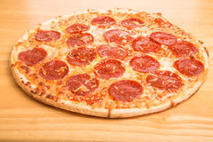 Whole Pepperoni Pizza on Wood Cutting Board Royalty Free Stock Images