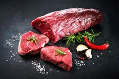 Whole piece of tenderloin with steaks and spices ready to cook o. Fresh and raw beef meat. Whole piece of tenderloin with steaks and spices ready to cook on dark Stock Photography