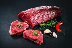 Whole piece of tenderloin with steaks and spices ready to cook o. Fresh and raw beef meat. Whole piece of tenderloin with steaks and spices ready to cook on dark Stock Image