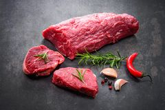 Whole piece of tenderloin with steaks and spices ready to cook o. Fresh and raw beef meat. Whole piece of tenderloin with steaks and spices ready to cook on dark Royalty Free Stock Image