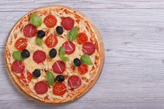 Whole pizza with salami, tomato, cheese, olives and basil Royalty Free Stock Photo